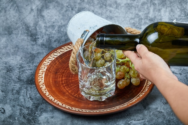 Kleiner eimer trauben in keramikplatte und hand gießen wein in das glas auf marmor. Kostenlose Fotos