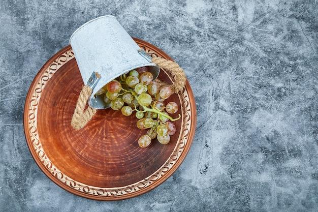 Kleiner eimer trauben innerhalb der keramikplatte auf einem marmorhintergrund. Kostenlose Fotos