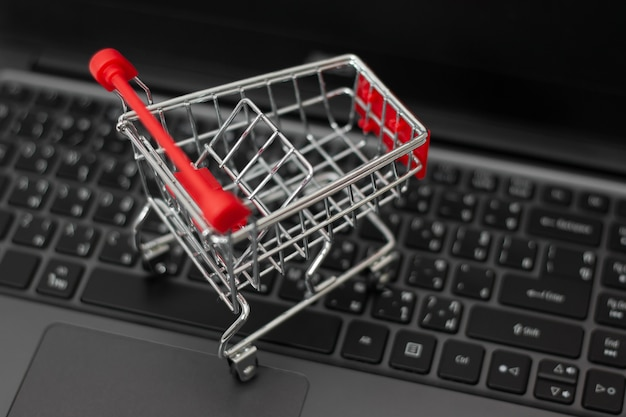 Kleiner einkaufswagen auf dem laptop für online-shopping. online-shopping-konzept. Premium Fotos