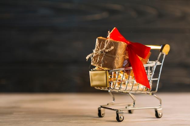 Kleiner einkaufswagen mit geschenkbox mit band Kostenlose Fotos