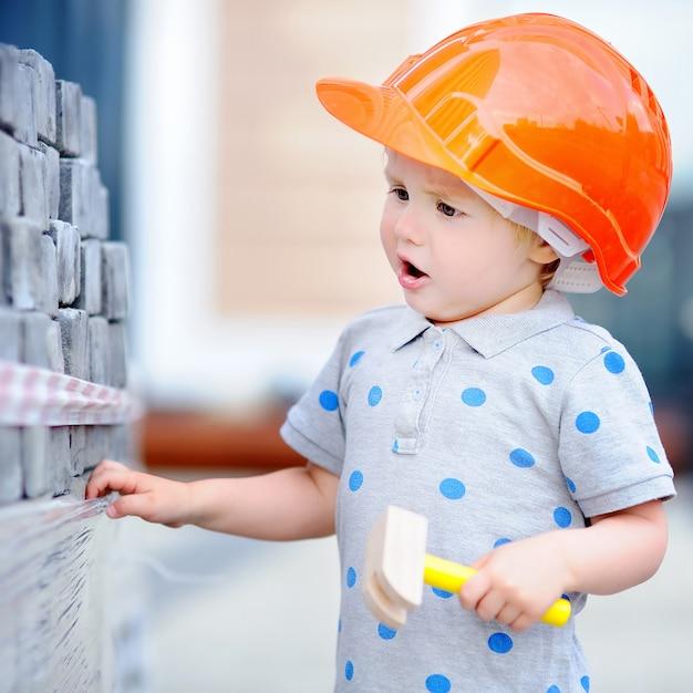 Kleiner erbauer in den hardhats mit dem hammer, der draußen arbeitet Premium Fotos