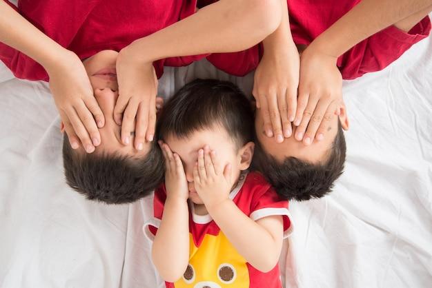 Kleiner geschwisterjunge legte sich auf dem bodenblick auf die kameraliebe nieder und glücklich Premium Fotos