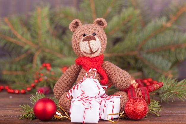 Kleiner gestrickter bär, ein neujahrsgeschenk, ein symbol des jahres. weihnachtsdekoration. Premium Fotos
