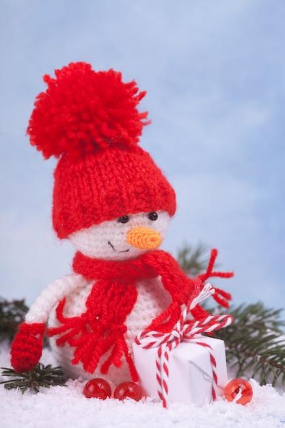 Kleiner gestrickter schneemann ein neujahrsgeschenk, ein symbol des jahres. weihnachtsdekoration. Premium Fotos