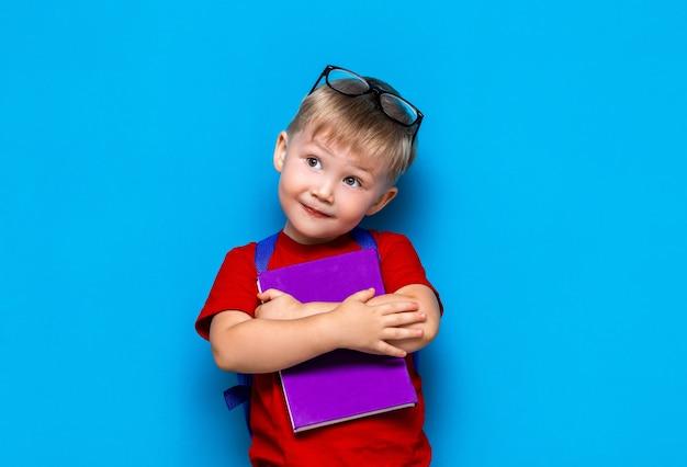 Kleiner glücklicher lächelnder junge mit gläsern auf seinem kopf, buch in den händen, schultasche auf seinen schultern. zurück zur schule. bereit zur schule Premium Fotos