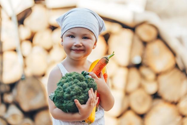 Kleiner glücklicher lächelnder landwirtjunge im weißen overall und in grauem hairband, die frisches organisches gemüse in den händen halten Premium Fotos