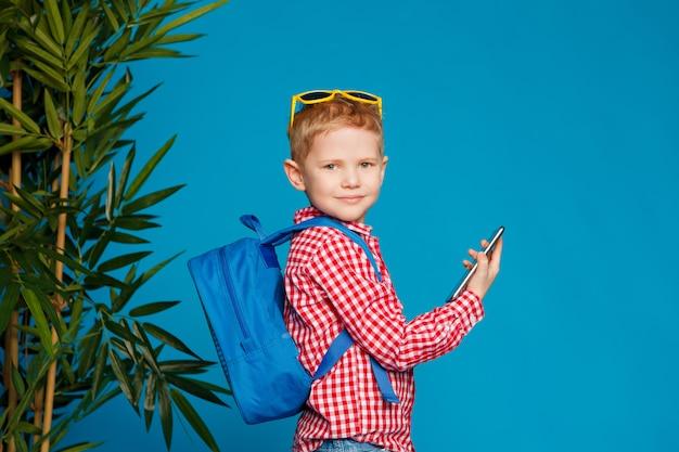 Kleiner hippie-junge mit dem rucksack und sonnenbrillen, die telefon halten Premium Fotos
