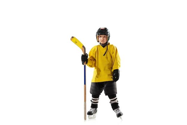 Kleiner hockeyspieler mit dem stock auf eisplatz und weißer studiowand Kostenlose Fotos