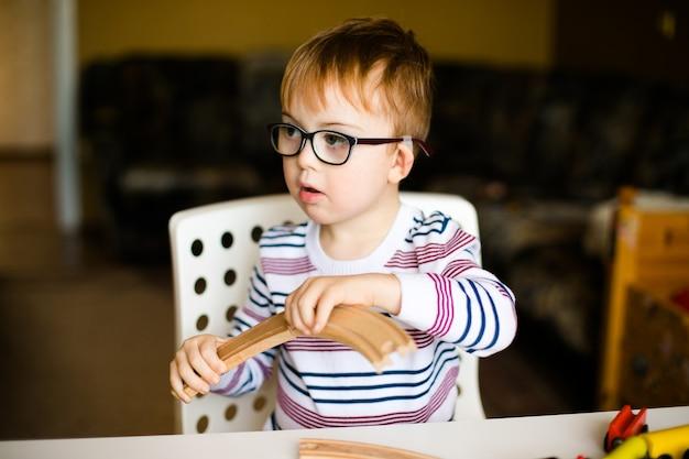 Kleiner ingwerkinderjunge in den gläsern mit der syndromdämmerung, die mit hölzernen eisenbahnen spielt Premium Fotos