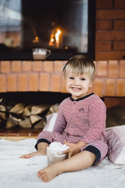 Kleiner junge am feuer und heiße schokolade mit marshmallows Kostenlose Fotos