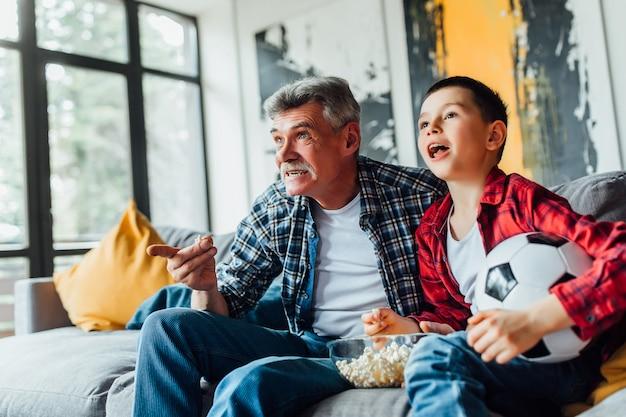 Kleiner junge auf couch mit großvater, zujubelnd für ein fußballspiel und einen fußballball halten. Premium Fotos