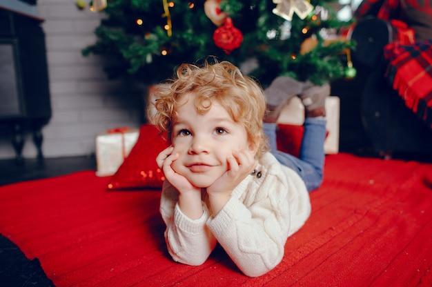 Kleiner junge cutte zu hause nahe weihnachtsdekorationen Kostenlose Fotos