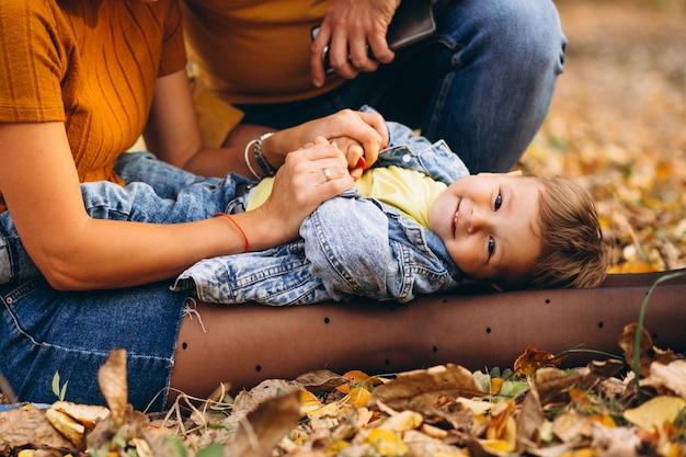 Kleiner junge, der auf den knien der mutter im park liegt Kostenlose Fotos