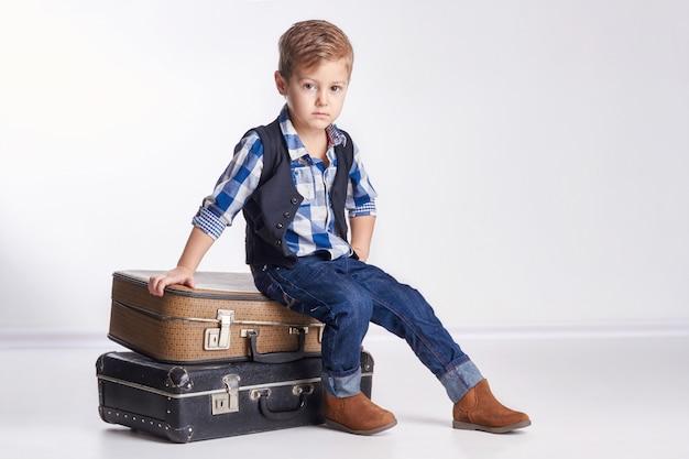 Kleiner junge, der auf den koffern, feiertag vorbereitend sitzt Premium Fotos