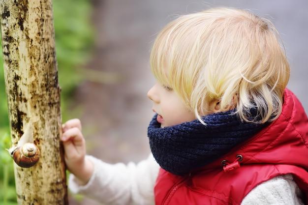 Kleiner junge, der auf großer schnecke während der wanderung im wald schaut Premium Fotos