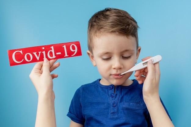Kleiner junge, der auf rotes papier mit mesaage coronavirus auf blauem hintergrund zeigt Premium Fotos