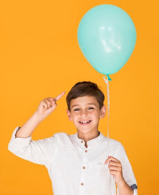 Kleiner junge, der auf seinen blauen ballon zeigt Kostenlose Fotos