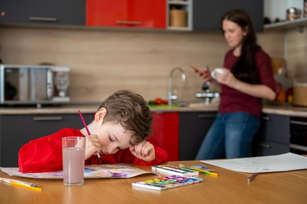 Kleiner junge, der bilder auf küche mit mutter zeichnet Premium Fotos