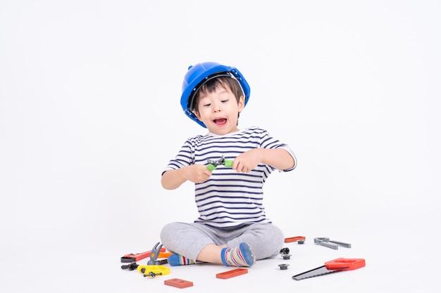 Kleiner junge, der den blauhelm sitzt und spielt mit baugerätspielzeug auf weiß trägt Kostenlose Fotos