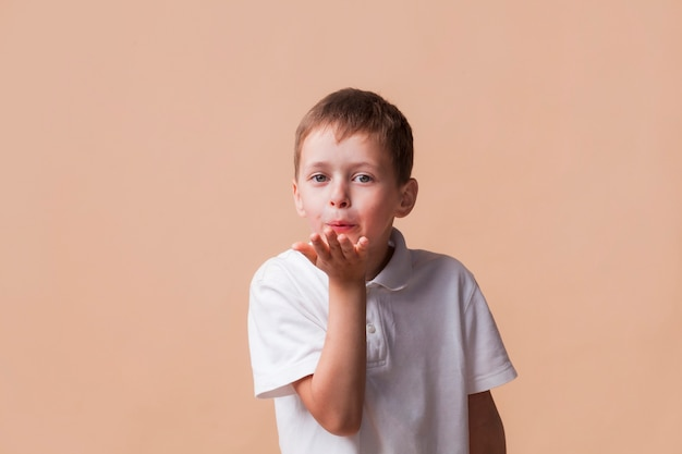 Kleiner junge, der die kamera durchbrennt einen kuss mit der hand auf luft betrachtet Kostenlose Fotos