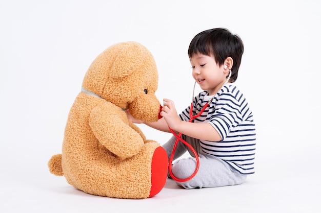 Kleiner junge, der doktor mit teddybären spielt Kostenlose Fotos