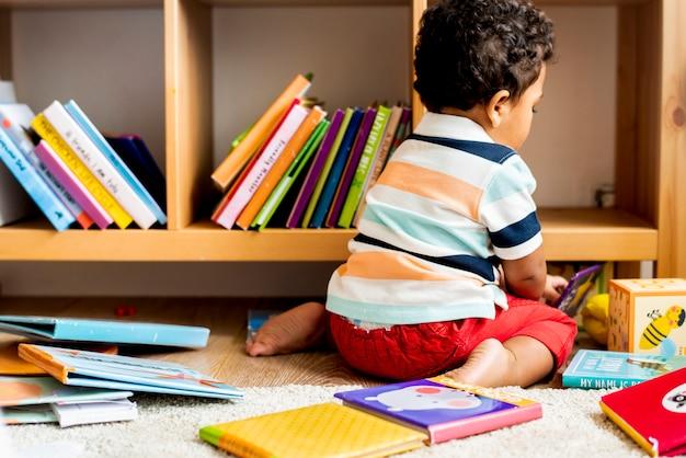 Kleiner junge, der ein buch an der bibliothek liest Premium Fotos