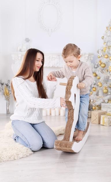 Kleiner junge, der ein papppferd nahe dem weihnachtsbaum reitet Premium Fotos