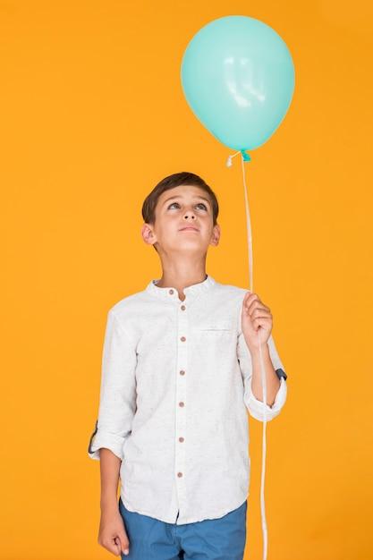 Kleiner junge, der einen blauen ballon betrachtet Kostenlose Fotos