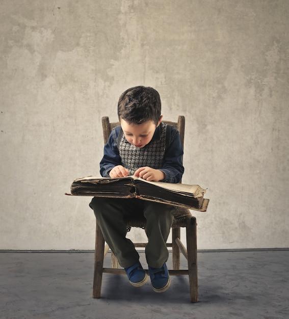 Kleiner junge, der einen kodex liest Premium Fotos