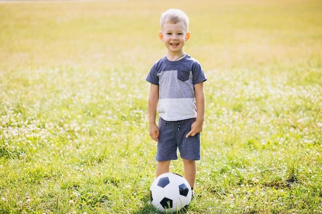 Kleiner junge, der fußball am feld spielt Kostenlose Fotos