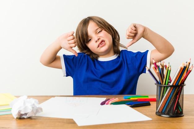 Kleiner junge, der hausaufgaben auf seinem schreibtisch unten zeigt daumen malt und tut und abneigung ausdrückt. Premium Fotos