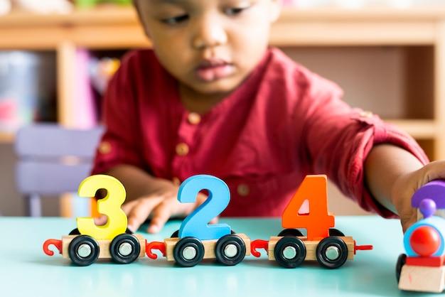 Kleiner junge, der hölzernes spielzeug der mathematik an der kindertagesstätte spielt Premium Fotos