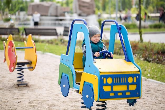 Kleiner junge, der in einem hölzernen auto auf dem spielplatz sitzt Premium Fotos