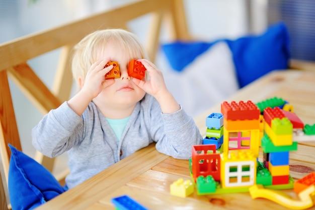 Kleiner junge, der mit bunten plastikblöcken am kindergarten oder zu hause spielt Premium Fotos