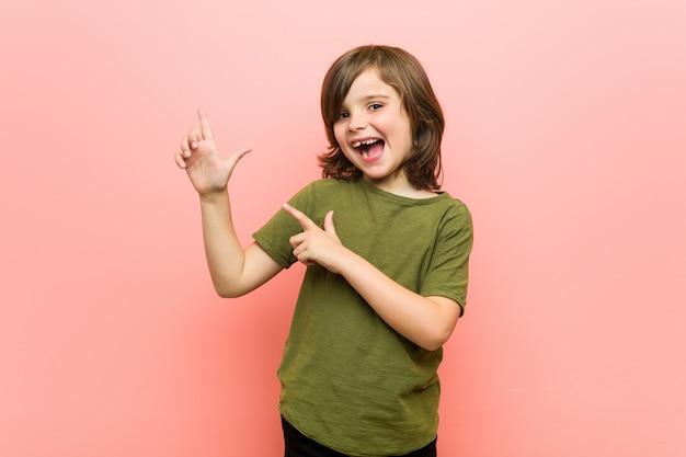 Kleiner junge, der mit den zeigefingern auf einen kopienraum zeigt und aufregung und wunsch ausdrückt Premium Fotos