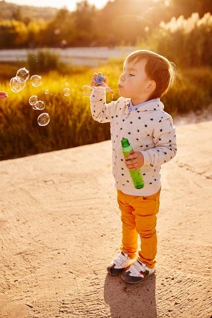 Kleiner junge, der mit seifenblasen spielt Kostenlose Fotos