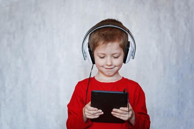 Kleiner junge, der musik von seiner tablette auf seinen kopfhörern hört Premium Fotos