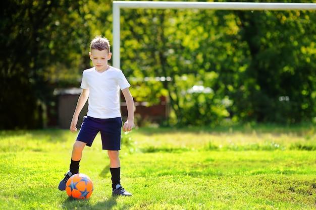 Kleiner junge, der spaß hat, ein fußballspiel am sonnigen sommertag zu spielen Premium Fotos
