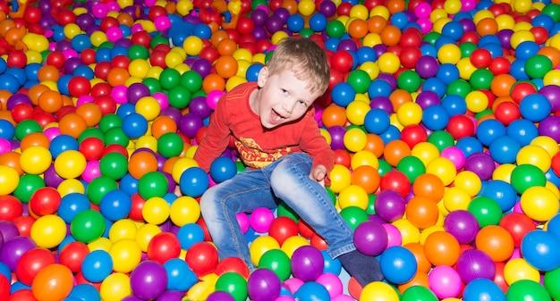Kleiner junge, der spaß in einem pool von bunten bällen im unterhaltungszentrum hat Premium Fotos