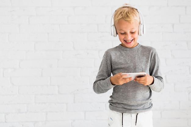 Kleiner junge, der spaß mit smartphone und kopfhörern hat Kostenlose Fotos