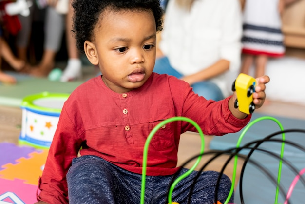 Kleiner junge, der spielwaren im spielzimmer spielt Premium Fotos