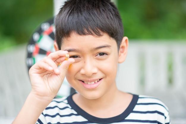 Kleiner junge, der tätigkeit der pfeilbrettfamilie im freien spielt Premium Fotos
