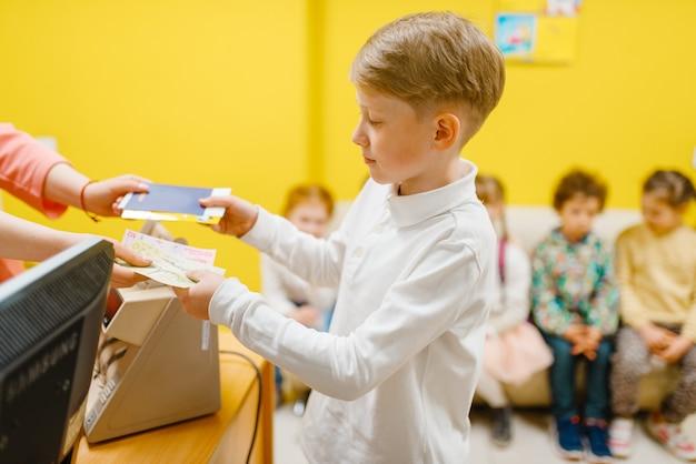 Kleiner junge, der ticket im spielzimmer kauft. Premium Fotos