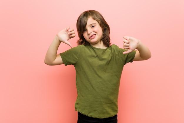 Kleiner junge, der unten daumen zeigt und abneigung ausdrückt. Premium Fotos