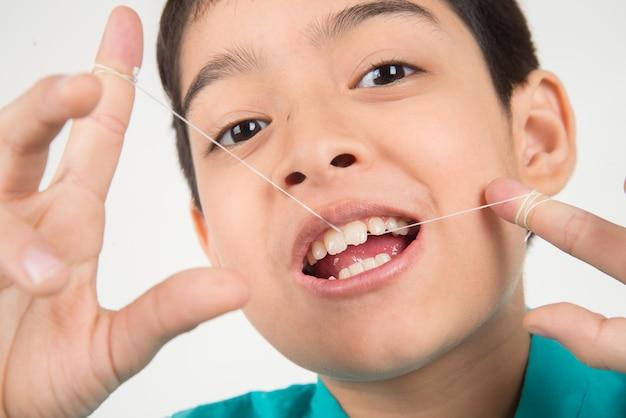 Kleiner junge, der zahnseide verwendet, um zahn zu säubern Premium Fotos