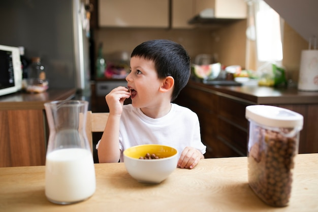 Kleiner junge, der zu hause frühstückt Kostenlose Fotos