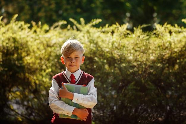 Kleiner junge, der zurück zur schule geht. kind mit rucksack und büchern am ersten schultag Premium Fotos