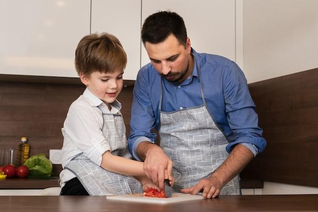 Kleiner junge des niedrigen winkels in der küche mit vater Kostenlose Fotos