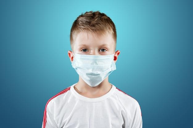Kleiner junge, ein kind in einer medizinischen maske auf einem blau Premium Fotos
