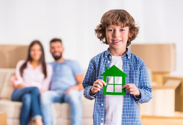 Kleiner junge hält ein papphaus in seinen händen. Premium Fotos